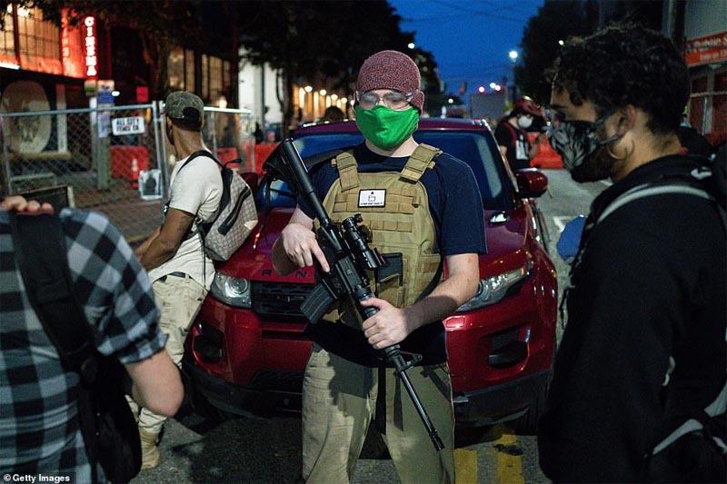 シアトルで小銃を持ち警備する男性