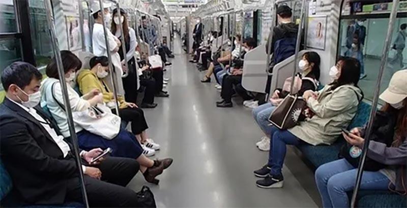 電車内でマスクする人々